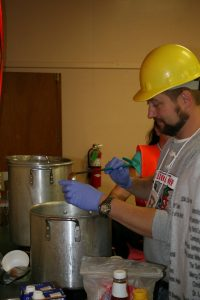 "Chris Weaver, a member of the TCMH EMS ""Road Kill Warriors"" team, ladles up a chili sample."