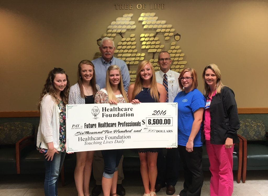 Scholarship recipients were, front row, left to right, Victoria Floyd; Megan Silveus; Sammy Garrett; Kelsey Drone; Stephanie Gentry, and Jenny Sawyer.  Making the presentation were, back row, Wes Murray, TCMH chief executive officer, and Jay Gentry, Healthcare Foundation director.