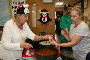 "Carol Honeywell serves up chili from ""Happy Feet"" a cook off team sponsored by Raymondville United Methodist Church."