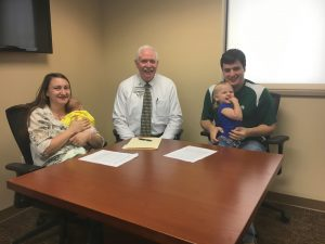 Dr. Jason and Dr. Teresa Loden have signed contracts to work full-time at TCMH.  Teresa Loden (far left) is a pediatrician, and Jason Loden (far right) is a general surgeon.  They are shown here with Wes Murray, CEO at TCMH.  The couple is holding their daughters—Gabriella, a newborn, and Elliana, age 2.  Both doctors will join the hospital in 2018.