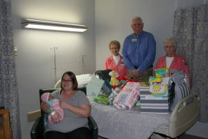 Sarah Dillin, seated, holds Hadley Rebecca Dillin, the first baby born at Texas County Memorial Hospital in 2017.  Presenting gifts to the Dillin family were (standing left to right) Roma Hollenbeck, TCMH Auxiliary; Wes Murray, TCMH CEO, and Julia Bryant, TCMH Auxiliary.