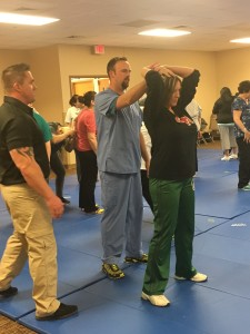 Patty Neal, a clerk in the Texas County Memorial Hospital business office, and Bryan Kemnitzer, a technologist in the radiology department, practice physical techniques for escape and control under the  oversight of a trainer from Mitigation Dynamics.